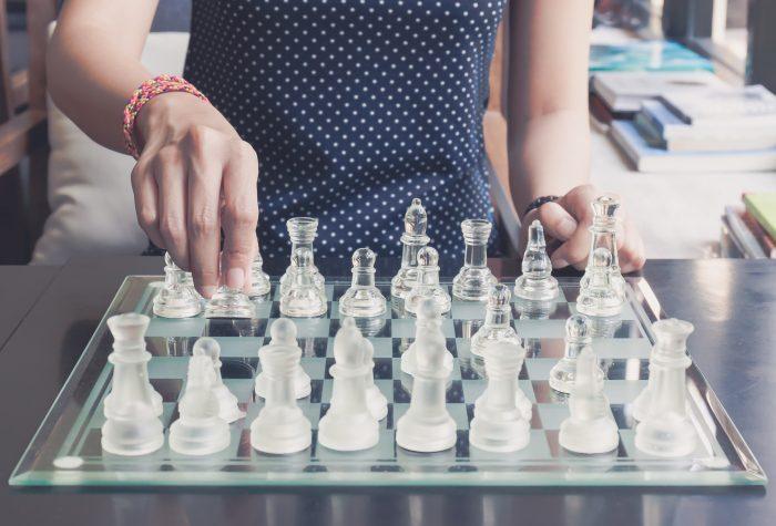 Close up of stylish woman playing modern chess board