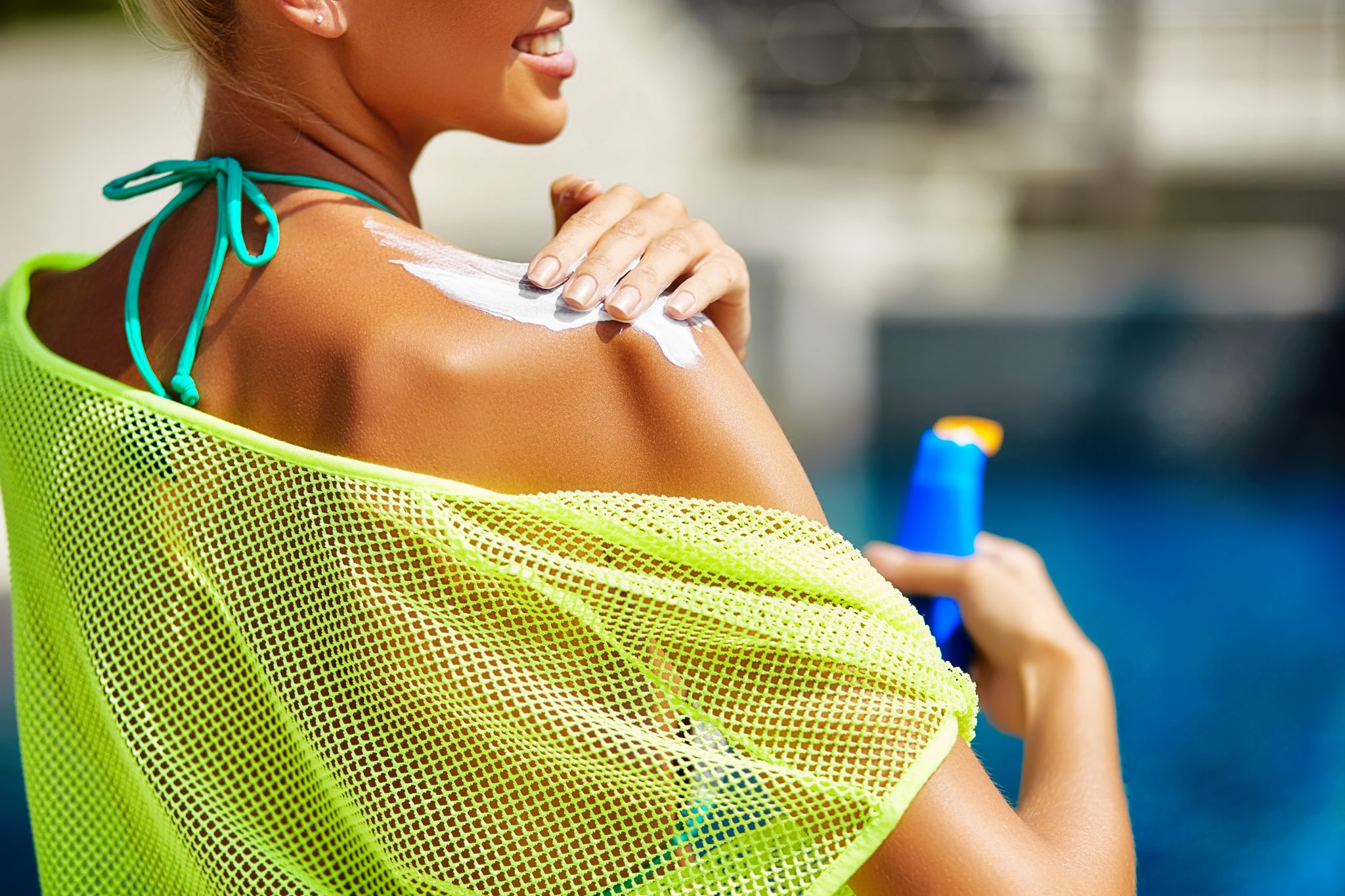 Blonde woman applying sunscreen